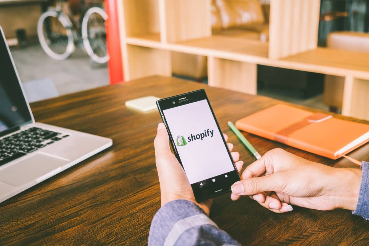Man holds Phone while viewing Shopify
